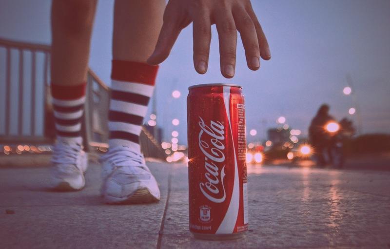 foto di una lattina di coca per strada